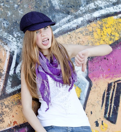 Grimacing teen girl near graffiti wall. photo