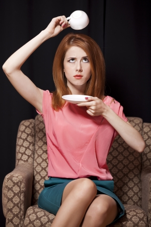 yearbook: Surprised redhead girl with cup of coffee. 70s