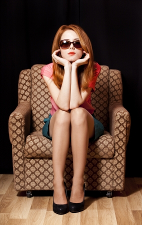 Redhead girl in armchair. 70s photo