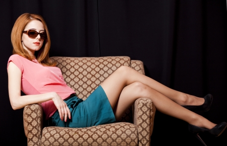 yearbook: Redhead girl in armchair. 70s