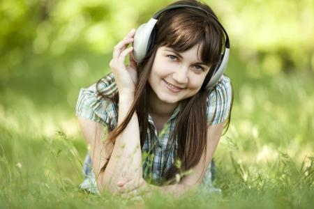 Young fashion girl with headphones at green spring grass. Stock Photo - 13624379