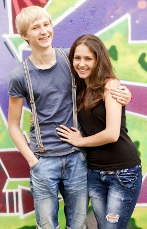 Style teen couple near graffiti background. photo