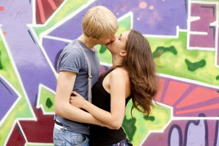 Young couple kissing near graffiti background. Stock Photo - 13665956