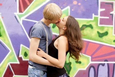 Young couple kissing near graffiti background. Stock Photo - 13665956