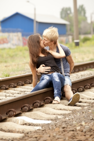 Couple kissing at railway. Urban photo. photo