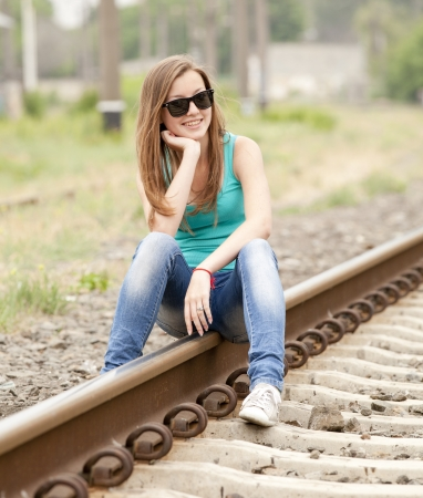 Young girl in glasses sitting at railway. photo