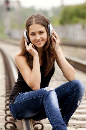 Teen girl with headphones at railways. photo