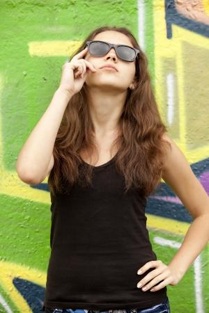 Style teen girl in sunglasses near graffiti background. photo