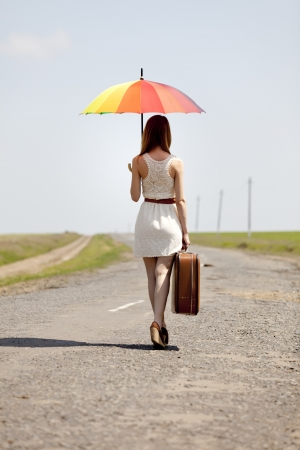 Young fashion girl with umbrella and suitcase at spring outdoor. photo