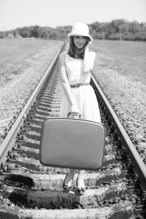 Young fashion girl with suitcase at railways. Photo in black and white style. Stock Photo - 13873466