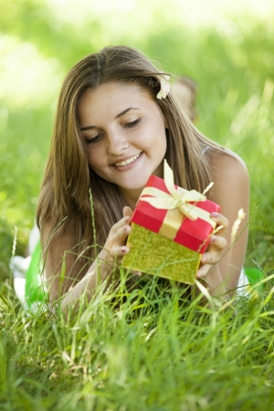 Surprised beautiful teen girl with gift in the park at green grass. photo
