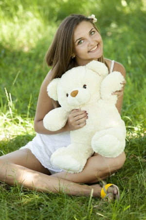 Beautiful teen girl with Teddy bear in the park at green grass. Stock Photo - 14011583