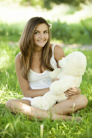 Beautiful teen girl with Teddy bear in the park at green grass. photo