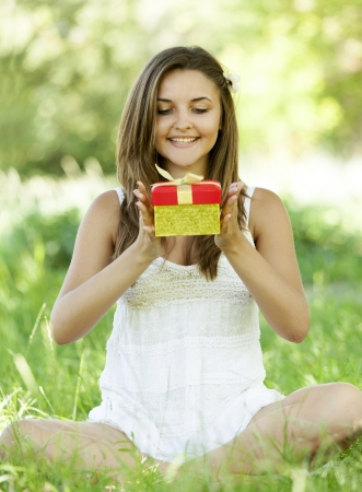 Beautiful teen girl with gift in the park at green grass. photo