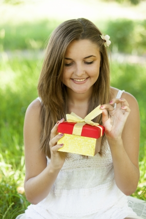 Beautiful teen girl with gift in the park at green grass. Stock Photo - 14011486