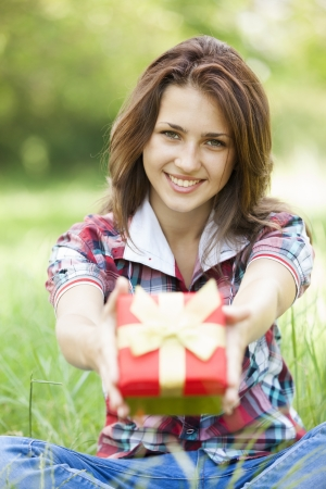 Beautiful teen girl with gift in the park at green grass photo