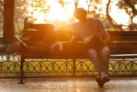 donna innamorata: Giovane coppia sulla panchina in strada. Archivio Fotografico