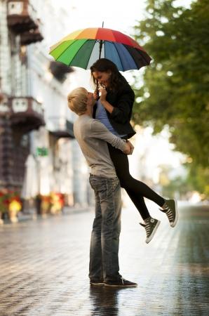 UOMO pioggia: Coppia giovane sulla strada della citt� con ombrello Archivio Fotografico