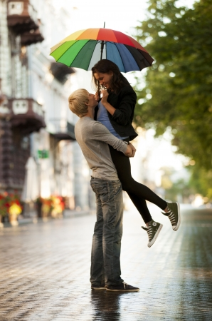 love in rain: Young couple on the street of the city with umbrella