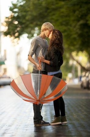 pareja adolescente: Pareja joven en la calle de la ciudad con el paraguas
