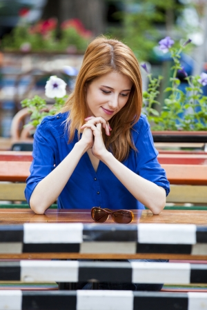 Style redhead girl sitting on the bench in the cafe photo