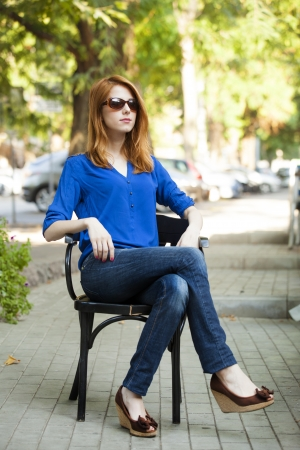 Style redhead girl sittin in the chair in the cafe photo