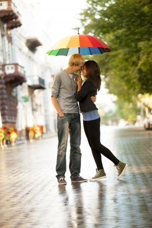lluvia paraguas: Pareja joven en la calle de la ciudad con el paraguas