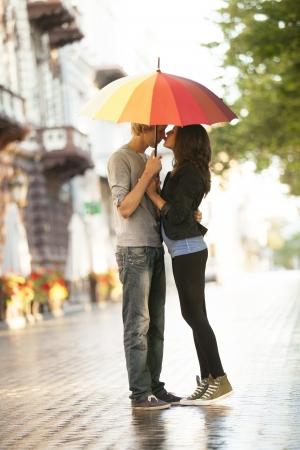 uomo sotto la pioggia: Coppia giovane sulla strada della città con ombrello Archivio Fotografico