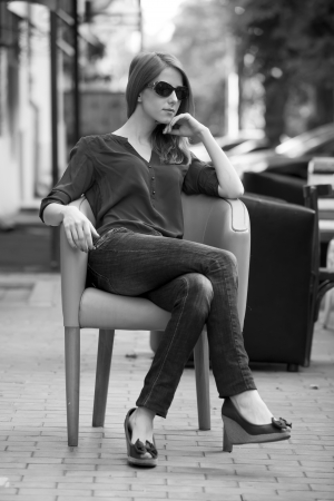 Style redhead girl sitting in the chair in the cafe.  photo