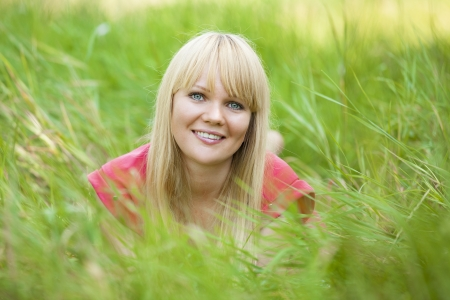 Blonde girl at green grass in the park. photo