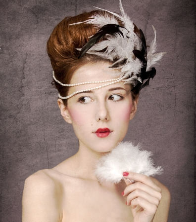 Redhead girl with Rococo hair style at vintage background. Photo in old style. photo