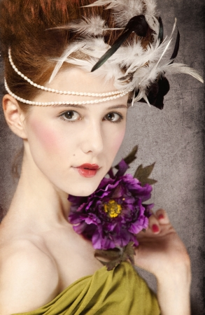 Redhead girl with Rococo hair style and flower at vintage background. Photo in old style. photo