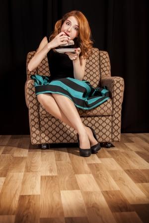 Redhead girl secretly eating cake. photo