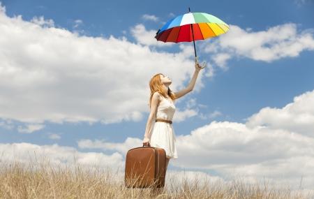 danza clasica: Chica pelirroja hermosa con el paraguas y la maleta en al aire libre. Foto de archivo