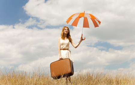 Beautiful redhead girl with umbrella and suitcase at outdoor. photo