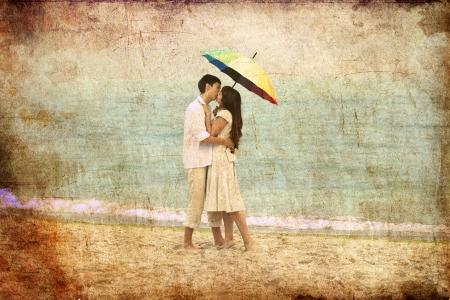 pareja besandose: Pareja bes�ndose bajo el paraguas en la playa. Foto en el estilo de la antigua imagen.