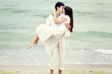 Couple kissing at the beach photo