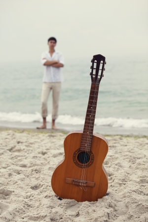 Men at the beach and guitar. photo