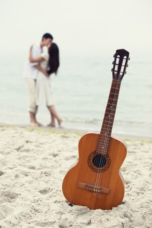 sexy couple on beach: Couple kissing at the beach and guitar.