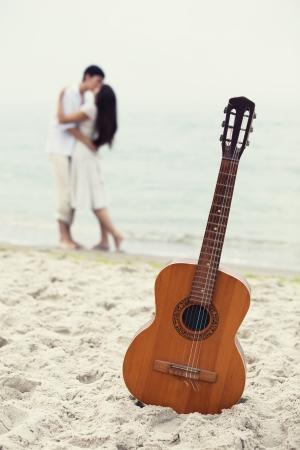 besos apasionados: Pareja bes�ndose en la playa y la guitarra. Foto de archivo