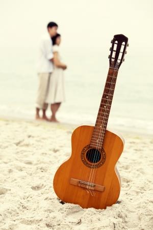 besos apasionados: Pareja besándose en la playa y la guitarra. Foto de archivo