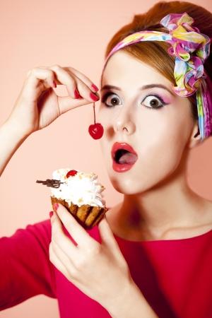 Style redhead girl with cake at pink background. Stock Photo - 14544889