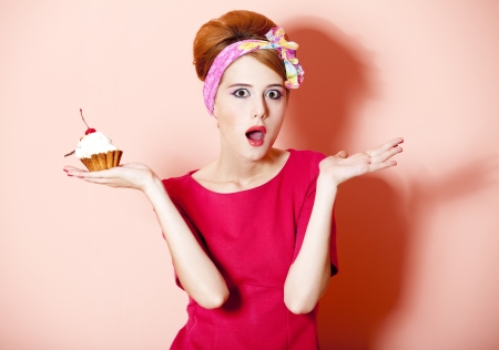Style redhead girl with cake at pink background. Stock Photo - 14544975