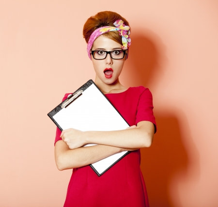 Style redhead girl in glasses and board at pink background. Stock Photo - 14544627