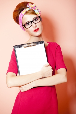 Style redhead girl in glasses and board at pink background. photo