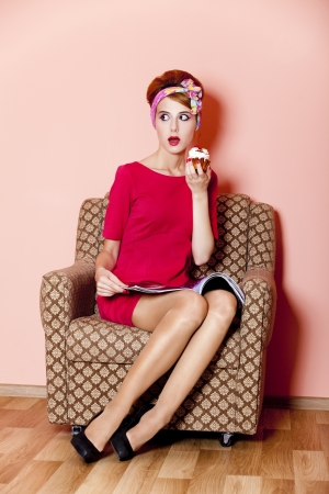 retro woman: Style girl in red dress sitting in armchair with cake and magazine