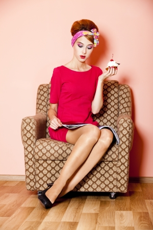 Style girl in red dress sitting in armchair with cake and magazine photo