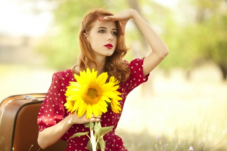woman freedom: Redhead girl with sunflower at outdoor.