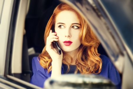 Beautiful redhead businesswoman calling by phone in the car. photo