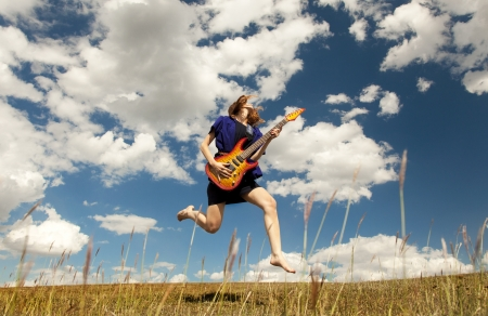 spring roll: Redhead girl jumping with guitar at outdoor.